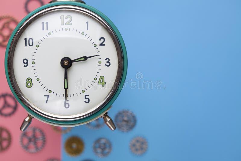 Despertador retro y pequeñas piezas del reloj en fondo coloreado imágenes de archivo libres de regalías