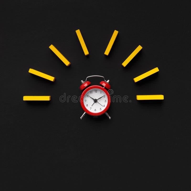 Despertador rojo con el bloque de madera amarillo en fondo negro imagen de archivo libre de regalías