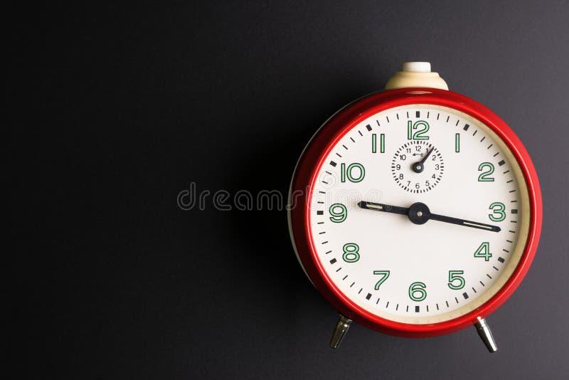 Despertador rojo en el fondo negro, concepto del tiempo, precipitación fotos de archivo libres de regalías