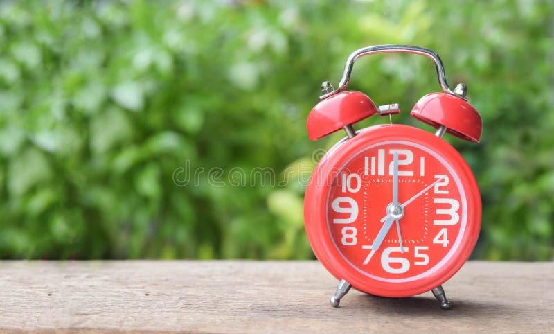 Despertador rojo en la tabla de madera y fondo verde con el espacio para el texto imagenes de archivo