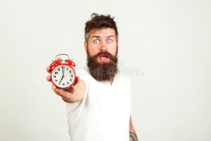 Despertador rojo y hombre borroso en el fondo blanco Concepto del plazo con el despertador barbudo chocado de la tenencia del hom fotos de archivo libres de regalías
