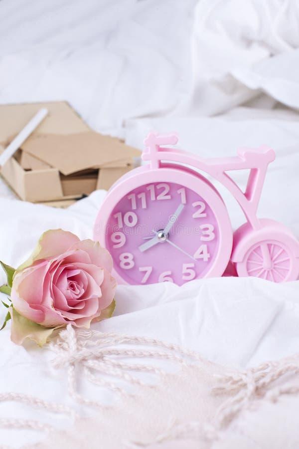 Despertador rosado, cama blanca y rosas rosadas Foto del vintage de la buena mañana Copie el espacio fotografía de archivo libre de regalías