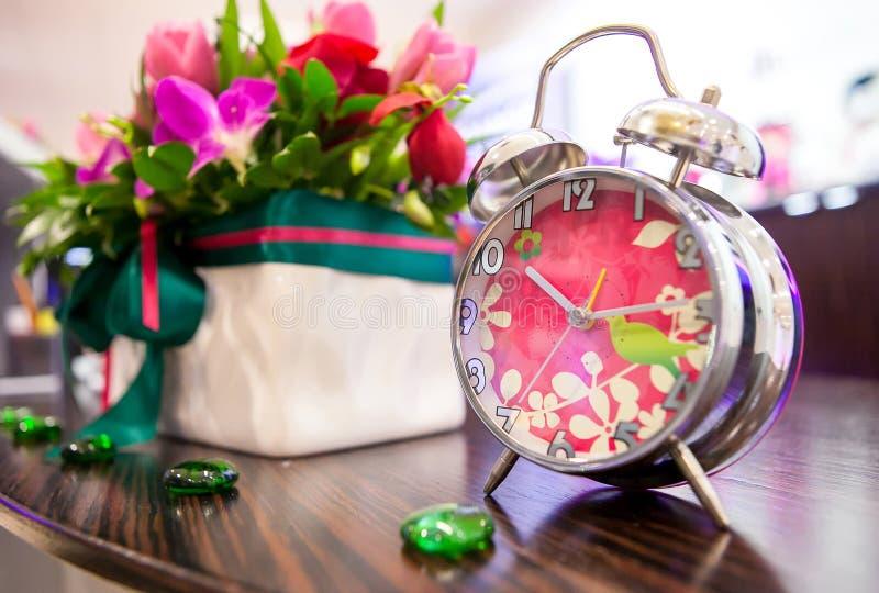 Despertador rosado decorativo en el interior imagen de archivo