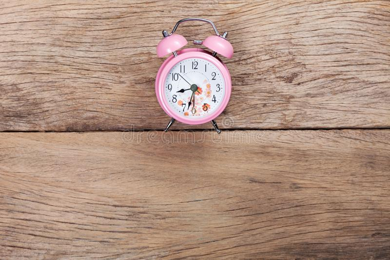 Despertador rosado hermoso en viejo fondo de madera fotos de archivo libres de regalías