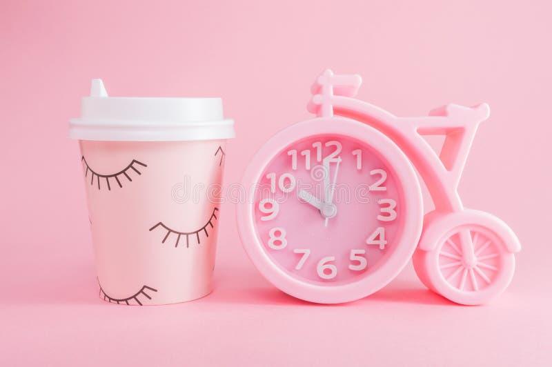 Despertador rosado y un vidrio de caf? para llevar en un fondo rosado Tiempo del caf? o buena ma?ana foto de archivo libre de regalías