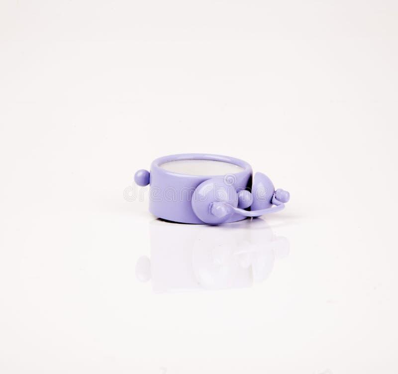 Despertador roxo bonito isolado no fundo branco fotografia de stock royalty free