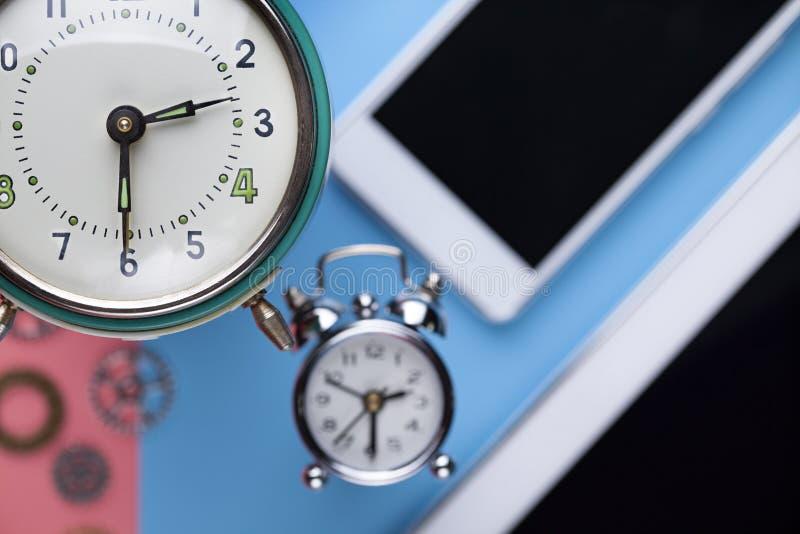 Despertador, smartphone y tableta en rosa y fondo azul imagen de archivo libre de regalías