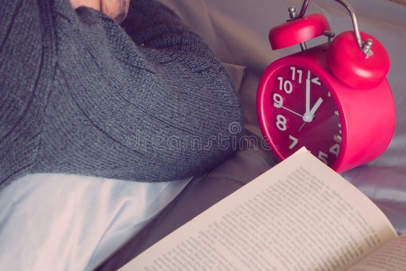 Despertador soñoliento de los hombres con la cama imagenes de archivo