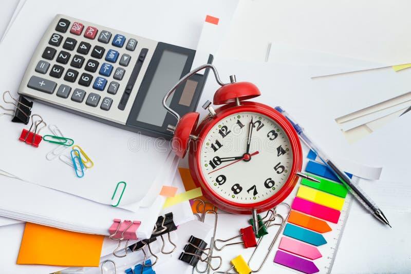 Despertador, sobre diversos documentos de la pila, negocio del plazo y conceptos de las finanzas imagen de archivo