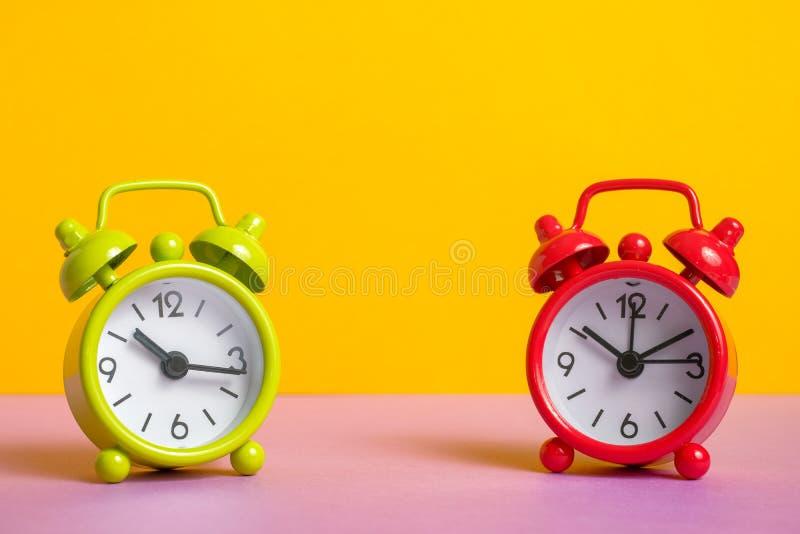 Despertador verde e vermelho do vintage no fundo amarelo da cor fotografia de stock royalty free