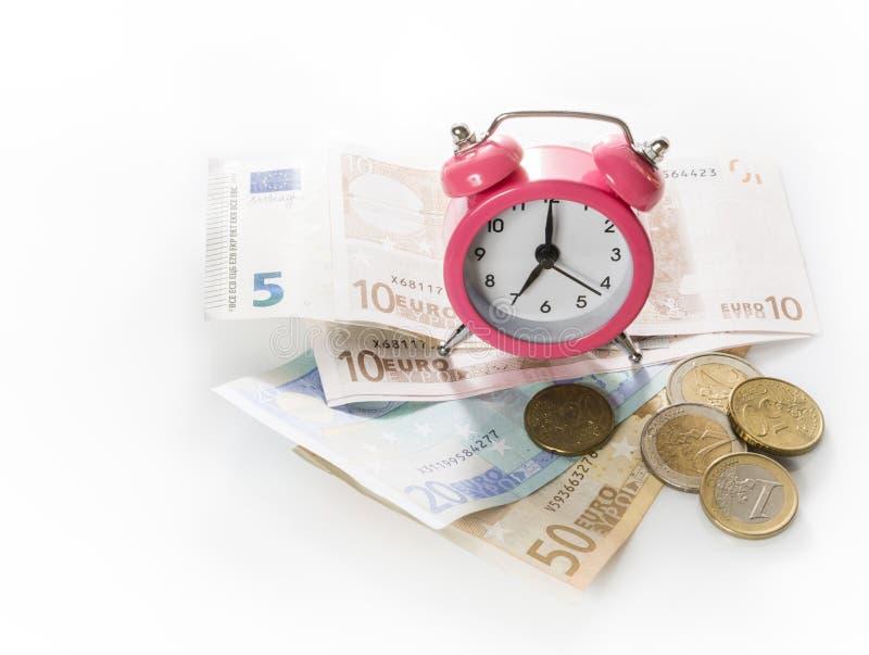 Despertador verde en el fondo de europrints y de monedas Aislado en el fondo blanco fotos de archivo libres de regalías