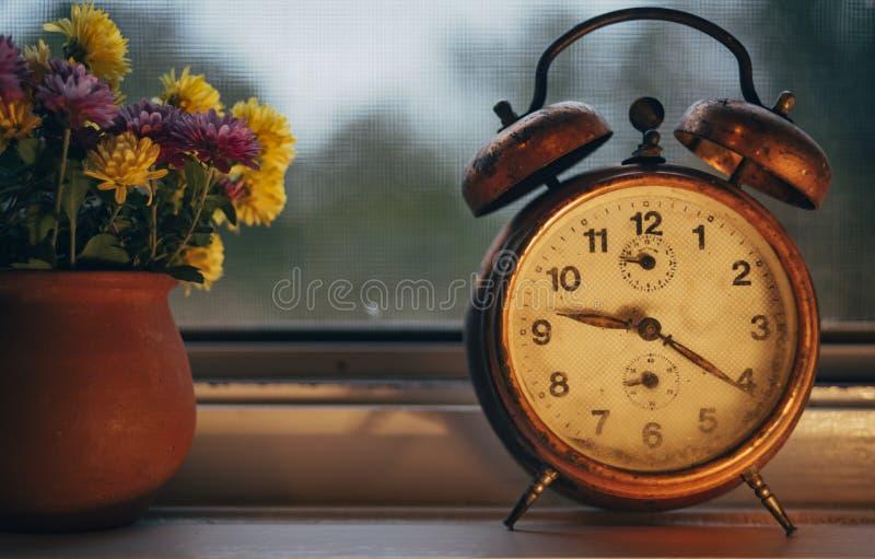 Despertador viejo en la ventana fotos de archivo libres de regalías