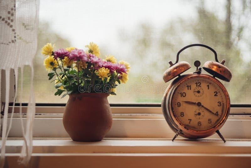 Despertador viejo en la ventana imagen de archivo libre de regalías