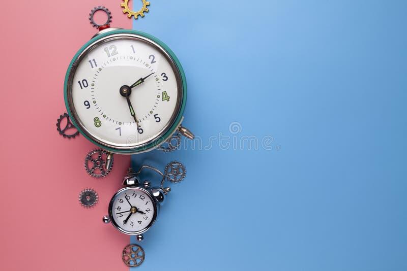 Despertador viejo y pequeño engranaje, pieza del reloj en un fondo dos-coloreado fotografía de archivo libre de regalías