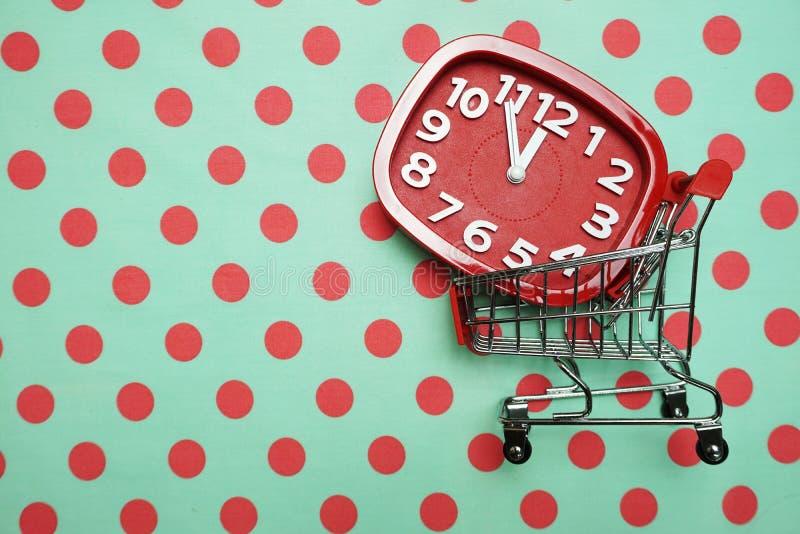 Despertador y carretilla rojos Mini Shopping Cart en fondo verde del lunar fotografía de archivo