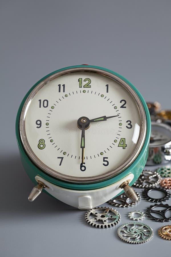 Despertador y engranajes viejos en fondo gris fotografía de archivo libre de regalías