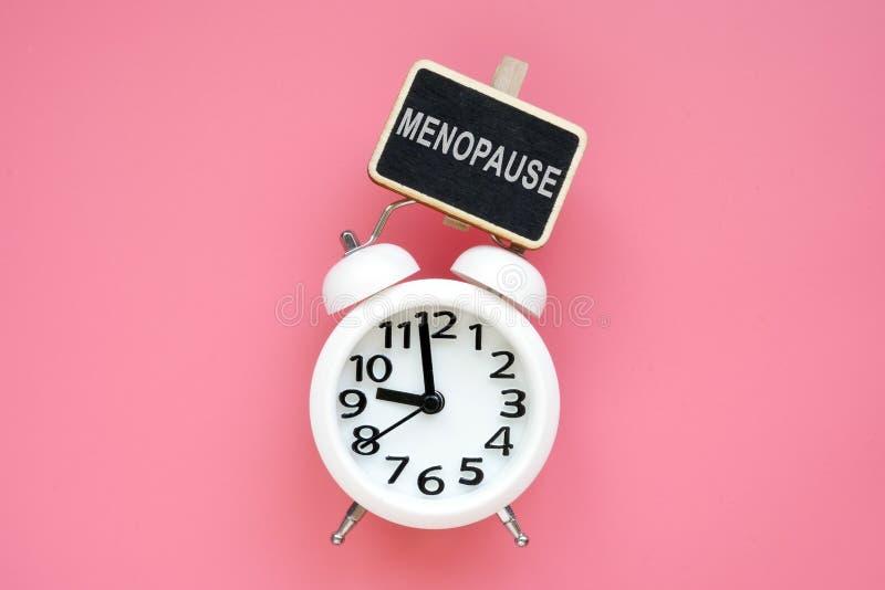 Despertador y menopausia de la palabra en un fondo rosado imagenes de archivo