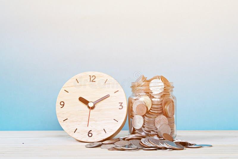 Despertador y monedas de madera en el fondo blanco imagenes de archivo