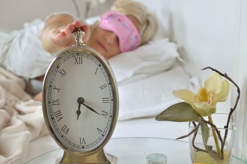 Despertador y mujer despierta fotografía de archivo libre de regalías