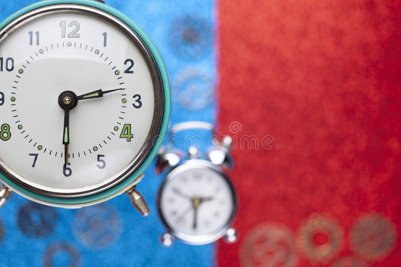 Despertador y pequeñas piezas del reloj en fondo abstracto rojo y azul foto de archivo