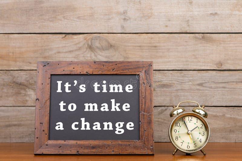 Despertador y pizarra con el texto y x22; It& x27; tiempo de s para hacer un change& x22; foto de archivo libre de regalías