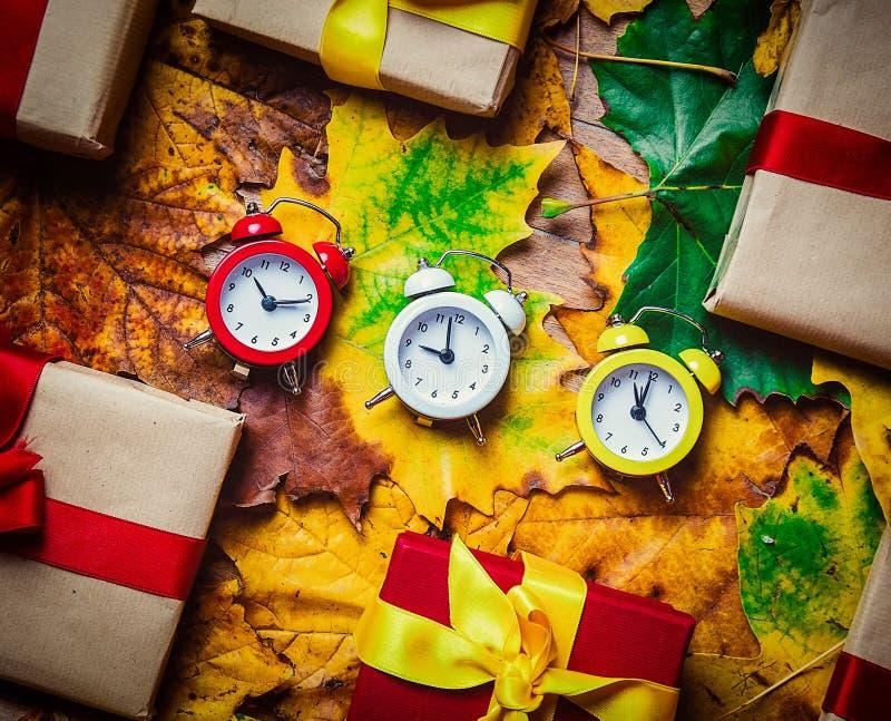 Despertadores e folhas de bordo do vintage com presentes de época natalícia fotos de stock