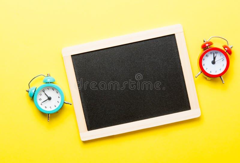 Despertadores e quadro-negro fotografia de stock