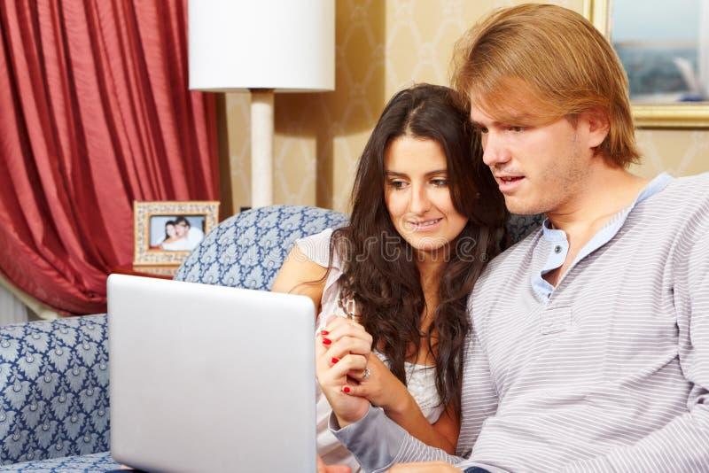 Despesa feliz dos pares com portátil imagem de stock
