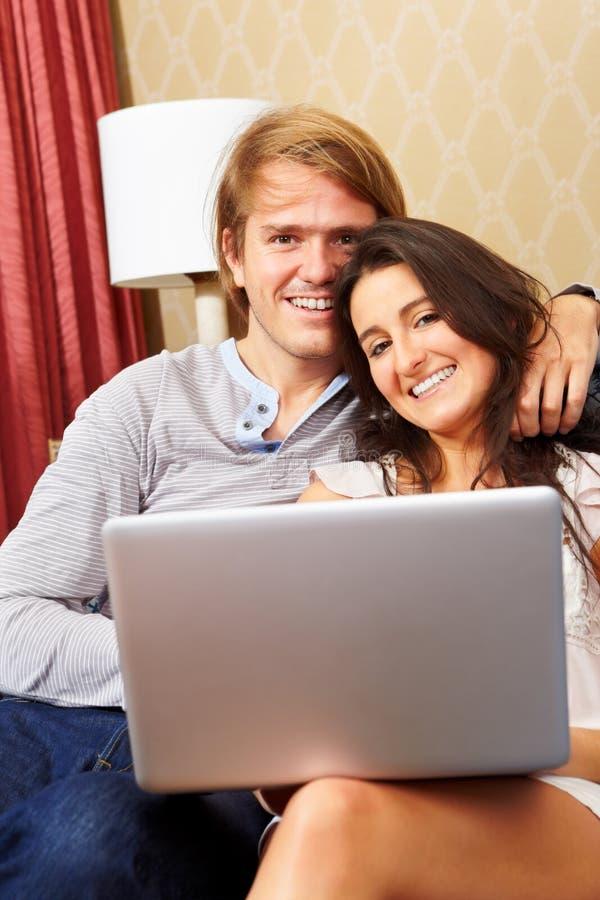 Despesa feliz dos pares com portátil fotografia de stock royalty free