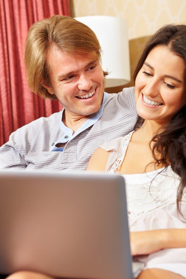 Despesa feliz dos pares com portátil imagem de stock royalty free