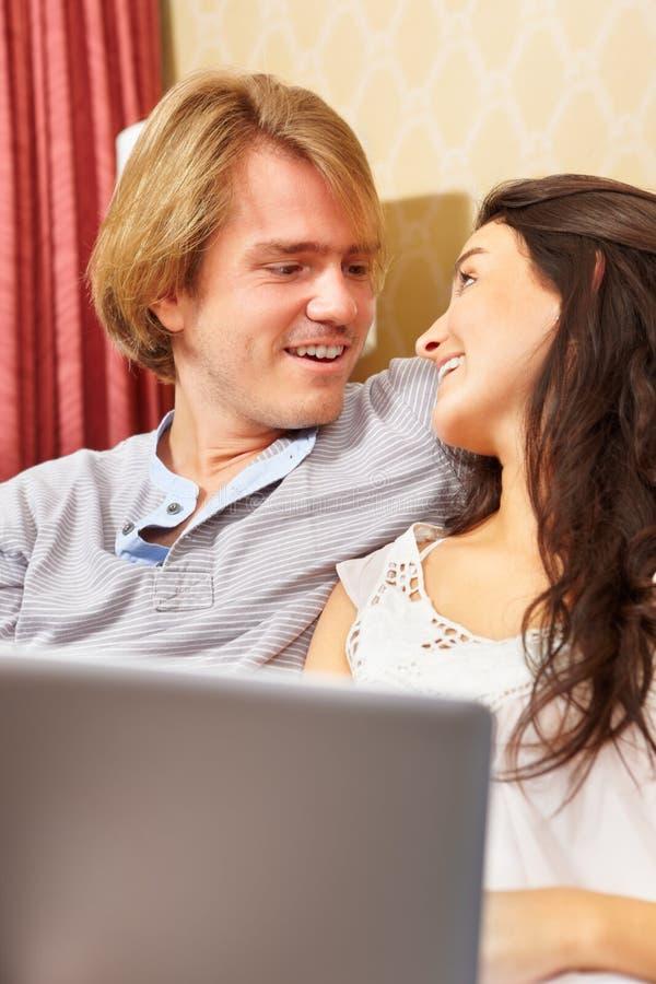 Despesa feliz dos pares com portátil foto de stock royalty free