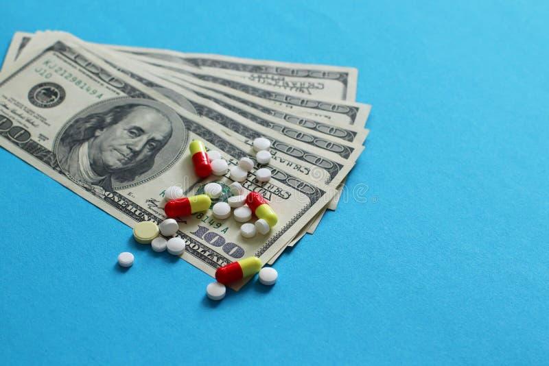 Despesas da medicina Comprimidos farmacêuticos dispersados da medicina no dinheiro do dólar isolado no fundo azul imagem de stock royalty free