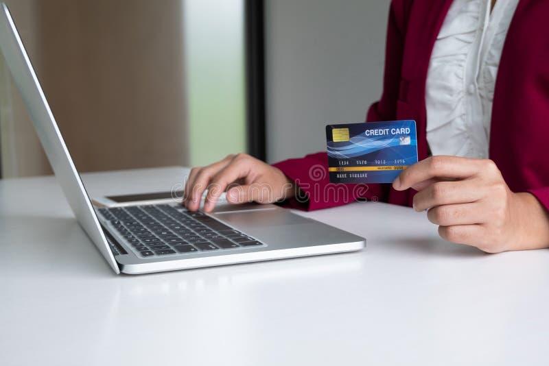 Despesas de consumo da mulher de negócio através do cartão de crédito e smartphone para a compra em linha em seu portátil foto de stock