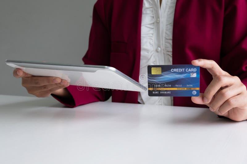 Despesas de consumo da mulher de negócio através do cartão de crédito e tabuleta para comprar em linha imagens de stock royalty free