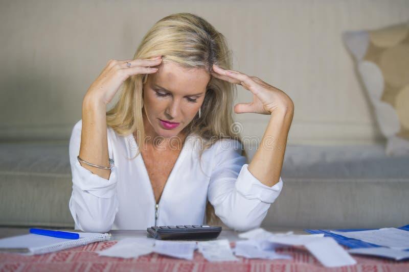 Despesas domésticas calculadoras do dinheiro da mulher loura preocupada e desesperada que fazem as contas do documento e de banco fotos de stock royalty free