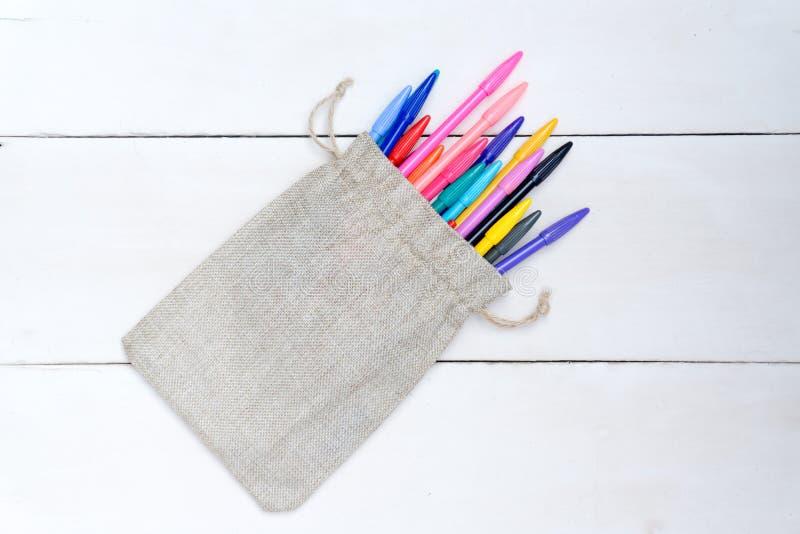 Despida el bolso con las plumas coloridas, en el bosque blanco imagen de archivo