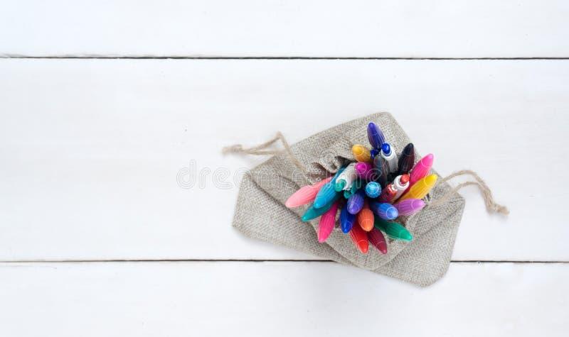 Despida el bolso con las plumas coloridas, en el bosque blanco foto de archivo