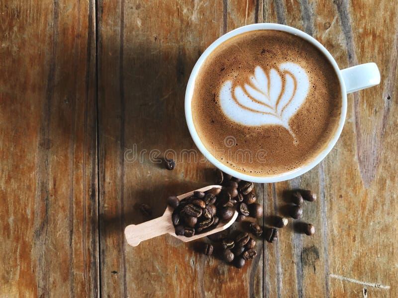 Despierte con café del arte del latte de la forma del amor en la taza blanca y los granos de café asados en cuchara en el vintage fotos de archivo
