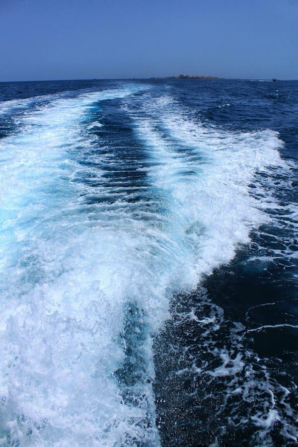 Despierte en el mar salido por un barco y una isla de Tabarca en el fondo fotografía de archivo