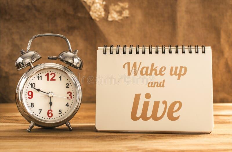 despierte y viva texto en el cuaderno con el despertador en la tabla de madera foto de archivo