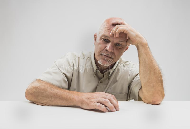 Despondent senior man sitting thinking. With his head on his hand staring down at the table with a serious expression stock photography
