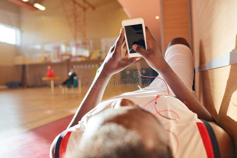 Desportista africano que escuta a música nos fones de ouvido no banco fotos de stock