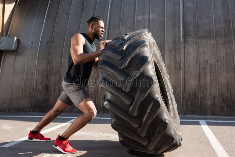 desportista afro-americano muscular que exercita com o pneu na rua foto de stock