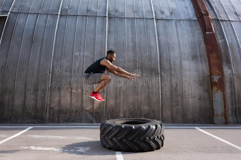 desportista afro-americano muscular que salta ao treinar com pneumático foto de stock royalty free