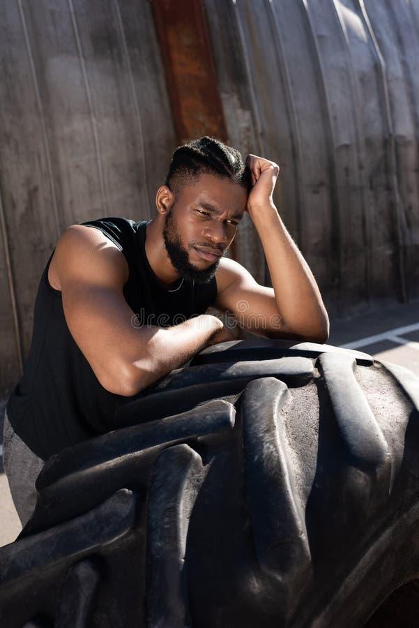 desportista afro-americano pensativo que inclina-se no pneumático e que olha afastado imagens de stock