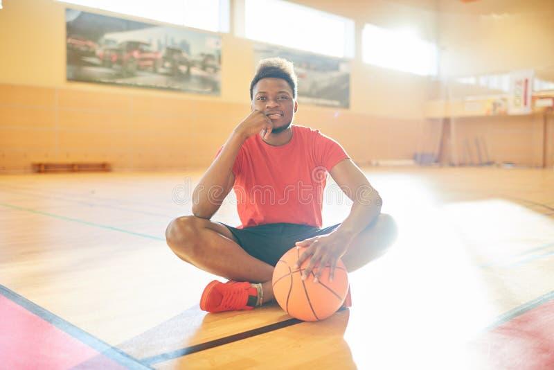 Desportista afro-americano que senta-se no assoalho da corte fotografia de stock royalty free