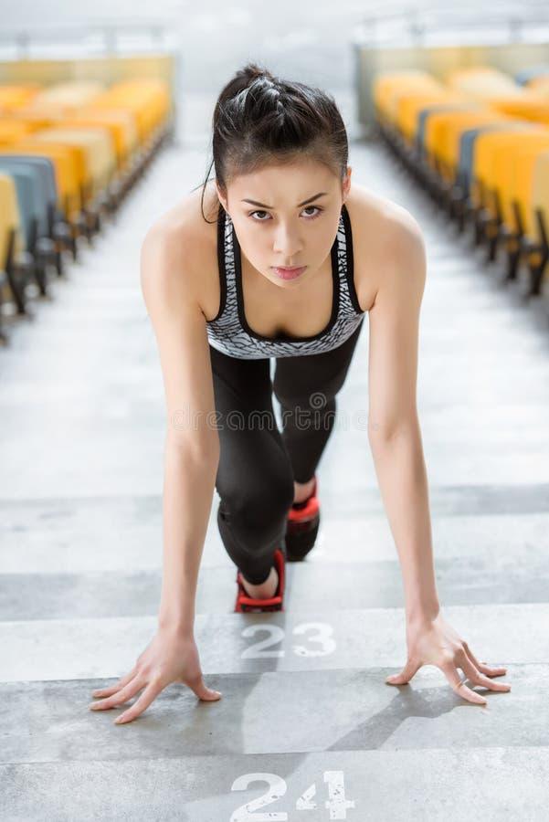 Desportista asiático novo na posição começar sobre escadas do estádio imagens de stock