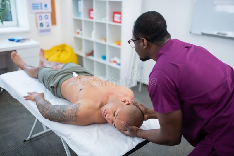 Desportista calvo que encontra-se sobre para trás ao ter a massagem para o pescoço imagem de stock