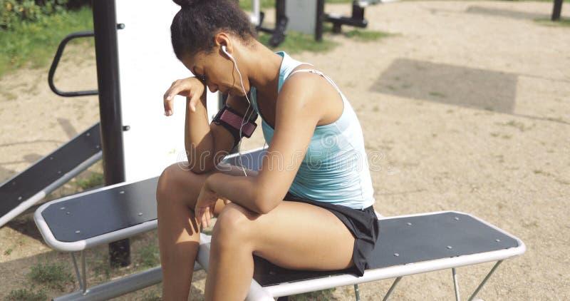 Desportista cansado no banco no parque foto de stock royalty free