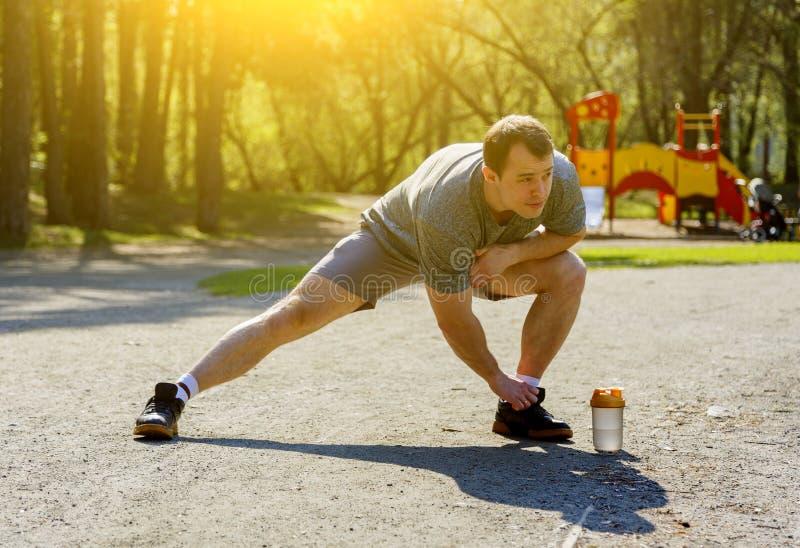 Desportista caucasiano saudável com a figura muscular que faz esticando o exercício antes da corrida imagens de stock royalty free